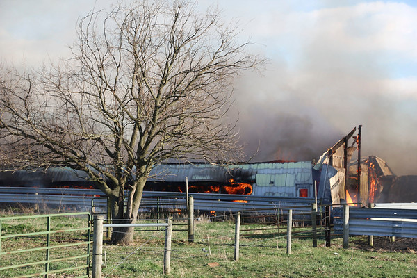 AIMEE AMBROSE | THE GOSHEN NEWS <br /> Fire, fueled by winds, destroyed a duck barn and two other buildings at a farm along C.R. 42 and C.R. 37 near Millersburg Tuesday.