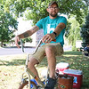 AIMEE AMBROSE | THE GOSHEN NEWS <br /> Austin Groves, Middlebury, pedals a makeshift bicycle to churn ice cream for a back-to-school party at The Post, 301 E. Lincoln Ave., sponsored by Harvest Community Church Saturday.