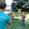 AIMEE AMBROSE | THE GOSHEN NEWS <br /> Turner Groves, 5, holds a racket with suckers on it to catch a ball thrown by Chris Yoder, Millersburg, during a back-to-school party at The Post, 301 E. Lincoln Ave., sponsored by Harvest Community Church Saturday.
