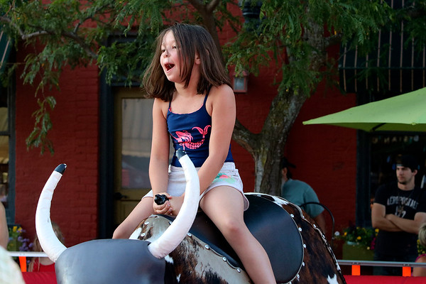 SHEILA SELMAN | THE GOSHEN NEWS<br /> Dakota Lewis holds on tight to the mechanical bull she's riding at First Fridays in downtown Goshen.