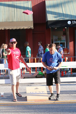 SHEILA SELMAN | THE GOSHEN NEWS<br /> Aaron Kandler of Paw Paw, Michigan, left, tosses a bag during a cornhole tournament during First Fridays in downtown Goshen Friday night. To his right is competitor Gary Cover, Goshen. Kandler was partnered with Dana Hill of Elkhart. Their team was named Team Cookies and Cream. Cover was partnered with Joey Diaz of Goshen. Their team name was Watch This. The duo of Kandler and Hill won the match.