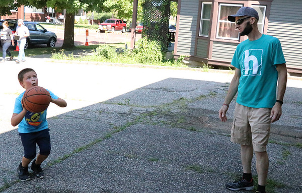 "AIMEE AMBROSE | THE GOSHEN NEWS <br /> Macen Riehl, 9, shoots a basketball while playing ""horse"" with Chuck Alleshouse, Goshen, during a back-to-school party at The Post, 301 E. Lincoln Ave., sponsored by Harvest Community Church Saturday."