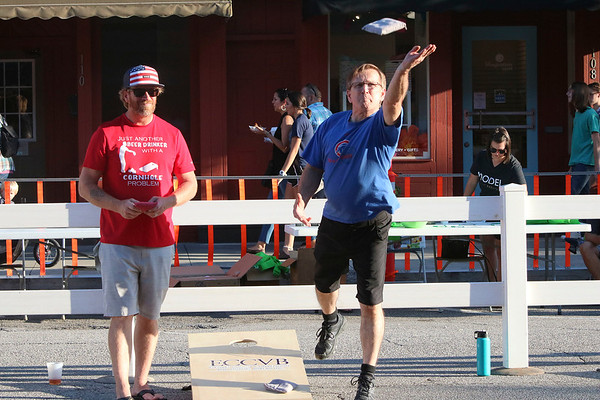 SHEILA SELMAN | THE GOSHEN NEWS<br /> Aaron Kandler of Paw Paw, Michigan, left, watches as Gary Cover of Goshen tosses a bag during a cornhole tournament during First Fridays in downtown Goshen Friday night. Kandler was partnered with Dana Hill of Elkhart. Their team was named Team Cookies and Cream. Cover was partnered with Joey Diaz of Goshen. Their team name was Watch This. The duo of Kandler and Hill won the match.