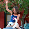 SHEILA SELMAN | THE GOSHEN NEWS<br /> Dakota Lewis raises her hand high to signal she's ready for a mechanical bull ride during First Fridays in downtown Goshen.