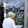 DENISE FEDOROW | THE GOSHEN NEWS<br /> A shopper looks over some of the photos in the Left Behind booth at the Amish Acres Arts & Craft Festival Thursday. Artist Kyle Wilson takes photos of abandoned buildings and items and using a technique that brings luminiscence to the photographs.