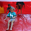 AIMEE AMBROSE | THE GOSHEN NEWS <br /> Children bound down a bouncy slide while playing at a back-to-school party at The Post, 301 E. Lincoln Ave., sponsored by Harvest Community Church Saturday.