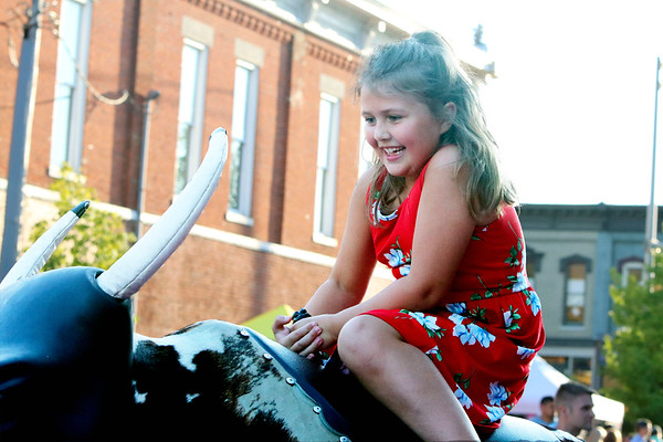 SHEILA SELMAN | THE GOSHEN NEWS<br /> Giavanna Park of Goshen grins in excitement as she rides the mechanical bull at First Fridays in downtown Goshen Friday night.