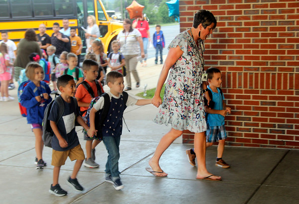 JOHN KLINE | THE GOSHEN NEWS<br /> Cori Willems, a kindergarten teacher at Jefferson Elementary School, second from right, leads a group of students into the school building during the first day of the new school year for Middlebury Community Schools early Wednesday morning.