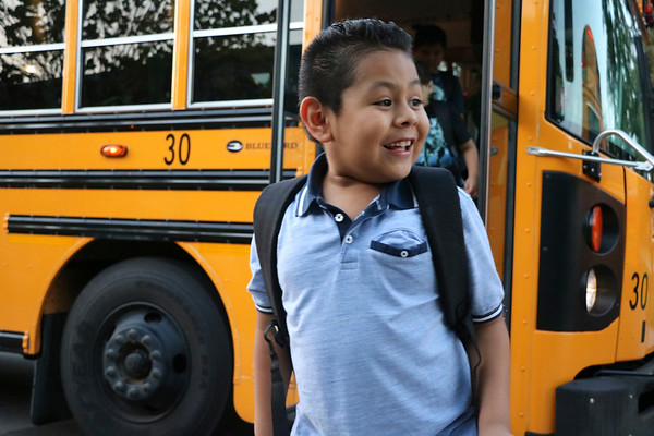 AIMEE AMBROSE | THE GOSHEN NEWS <br /> Erick Giron-Morales gets off his bus, ready to start second grade at Concord West Side Elementary School on the first day of the new school year Wednesday.