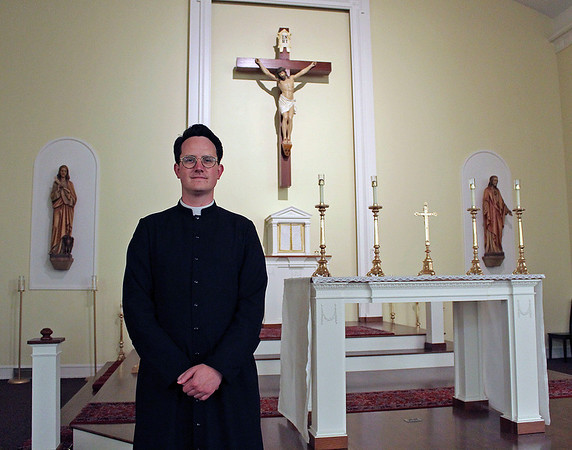 CAMDEN CHAFFEE   THE GOSHEN NEWS<br /> Father Royce Gregerson stands in the sanctuary of St. John the Evangelist Catholic Church in Goshen Tuesday. The church has experienced growth due to Hispanics moving to the parish.