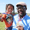 AIMEE AMBROSE | THE GOSHEN NEWS <br /> Idris Busari, a volunteer with Radio Horizonte in Goshen, holds his son Money Busari while they show their medals from the Great Inflatable Race at the Elkhart County Fairgrounds Saturday.