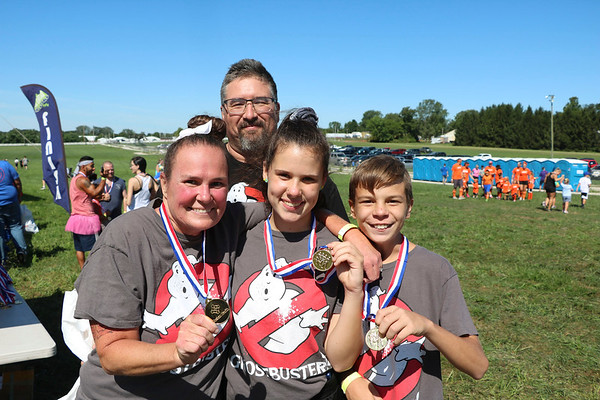 AIMEE AMBROSE   THE GOSHEN NEWS <br /> Bobbi Smith and her children, Andi and Ryan McClain, hold up the medals they received for completing the Great Inflatable Race and its course of about 10 bouncy obstacles at the Elkhart County Fairgrounds Saturday. Behind them is Dee Arnett, Smith's partner, who supported the team through the course.