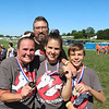 AIMEE AMBROSE | THE GOSHEN NEWS <br /> Bobbi Smith and her children, Andi and Ryan McClain, hold up the medals they received for completing the Great Inflatable Race and its course of about 10 bouncy obstacles at the Elkhart County Fairgrounds Saturday. Behind them is Dee Arnett, Smith's partner, who supported the team through the course.
