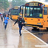 Roger Schneider   The Goshen News<br /> Goshen Middle School students run to their buses as a downpour strikes at the end of the school day Monday.
