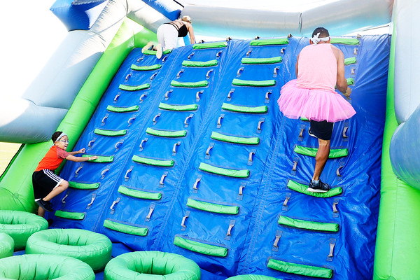 """AIMEE AMBROSE   THE GOSHEN NEWS <br /> A man and a boy race up the ladder side of the """"Castle of Doom"""" obstacle during the Great Inflatable Race at the Elkhart County Fairgrounds Saturday."""