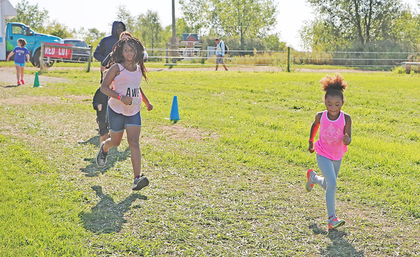 AIMEE AMBROSE   THE GOSHEN NEWS <br /> A group runs along the course between the first and second obstacles of the Great Inflatable Race at the Elkhart County Fairgrounds Saturday.