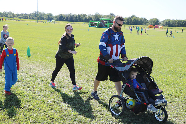 AIMEE AMBROSE   THE GOSHEN NEWS <br /> A family, with a boy in a Super Mario costume and a man in a Captain America shirt, walk toward the next obstacle along the course of the Great Inflatable Race at the Elkhart County Fairgrounds Saturday.