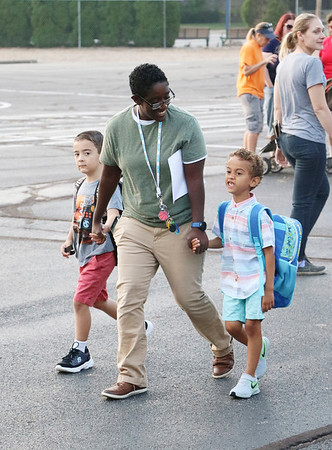 JOHN KLINE | THE GOSHEN NEWS<br /> A Chandler Elementary School employee helps students find their new classrooms during the first day of school for Goshen Community Schools early Wednesday morning.