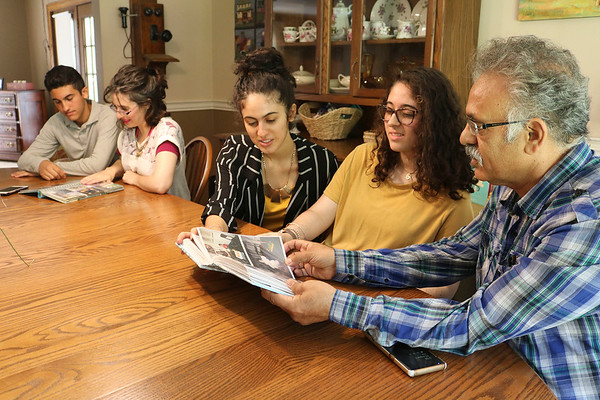 JOHN KLINE | THE GOSHEN NEWS<br /> Abbas Kermani, who immigrated to the United States from Iran in the early 1970s, right, looks at old family photos from Iran with, from left, son Soroosh, 15, wife Tamara, and daughters Mansoorah, 18, and Aameneh, 17, during a visit to their home in Millersburg Aug. 2.