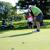 SHEILA SELMAN | THE GOSHEN NEWS<br /> Mark Podgorski of Goshen Health sinks a putt while teammate Matt Schrock with DJ Construction looks on. The two were golfing Thursdsay morning at Maplecrest Country Club as part of the Goshen Chamber of Commerce Golf Outing.