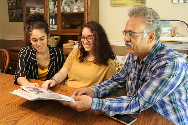 JOHN KLINE | THE GOSHEN NEWS<br /> Abbas Kermani, who immigrated to the United States from Iran in the early 1970s, right, looks at old family photos from Iran with his daughters, from left, Mansoorah, 18, and Aameneh, 17, during a visit to their home in Millersburg Aug. 2.