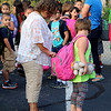 JOHN KLINE | THE GOSHEN NEWS<br /> Debbie Hostetler, a paraprofessional at Chandler Elementary School, left, helps a student with her backpack during the first day of school for Goshen Community Schools early Wednesday morning.