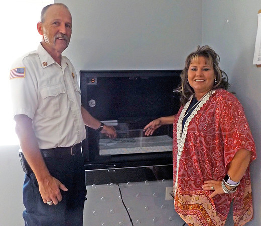 Denise Fedorow | The Goshen News<br /> Turkey Creek Township FIre Chief Mickey Scott, left,  and Safe Haven Baby Box Founder Monica Kelsey, show what the inside of the baby box looks like.