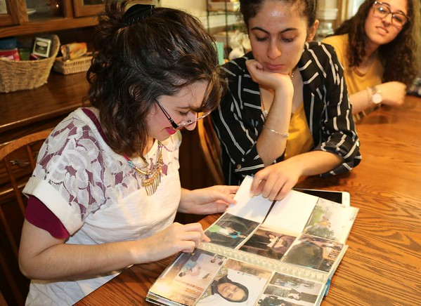 JOHN KLINE | THE GOSHEN NEWS<br /> Tamara Kermani, wife of Abbas Kermani, who immigrated to the United States from Iran in the early 1970s, left, looks at old family photos from Iran with daughters, from left, Mansoorah, 18, and Aameneh, 17, during a visit to the family's Millersburg home Aug. 2.