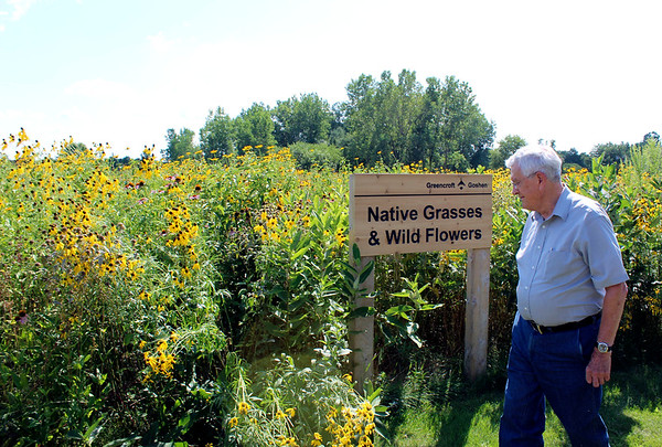 CAMDEN CHAFFEE | THE GOSHEN NEWS<br /> Gordon Cunningham walks the prairie on the Greencroft Goshen campus Wednesday. Cunningham enjoys hiking through the prairie twice a day in addition to caring for the wildlife that inhabits the 2-3 acres.
