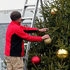 Roger Schneider | CNHI News Indiana<br /> Cory Owens of Second Nature Landscaping & Christmas Decor, places an ornament on a Christmas tree along Zionsville's Main Street on Nov. 29 in preperation for the town's Christmas parade the next day. The parade was canceled due to the cold, rainy weather. A local retailer says weather plays a role in how many shoppers she has each holiday season.