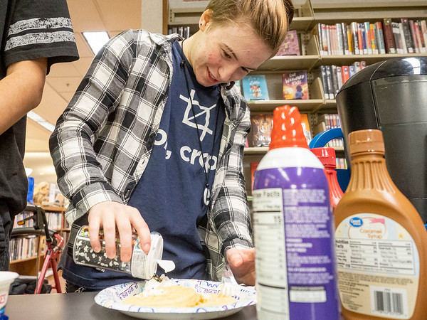 Joseph Weiser   The Goshen News<br /> Andrew Batchelor, 15, of Goshen, adds sprinkles to their waffles during the Teen Cafe: Waffle Bar Thursday at the Goshen Public Library. The students were given two waffles to top with a variety of toppings including whipped cream, butter, caramel, chocolate syrup, mini chocolate chips, strawberry syrup and sprinkles.
