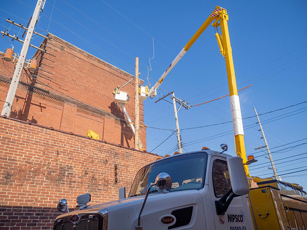 Northern Indiana Public Service Co. linemen install a new power pole in the alley behind the Goshen Theater at 216 S. Main St., Goshen, for service upgrades Tuesday.