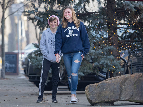 Cohem Silveus, 11, left, and Eliza Silveus, 14, right, both of Warsaw, walk Monday in front of the Goshen Christmas tree at the intersection of Main Street and West Washington Street adjacent to Reverie Yarn, Decor & Gifts.