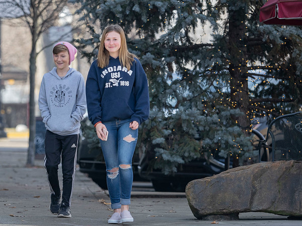 Cohem Silveus, 11, left, and Eliza Silveus, 14, right, both of Warsaw, walks in front of the Goshen Christmas tree at the intersection of Main St. and W. Washington St. adjacent to Reverie~Yarn, Decor & Gifts.