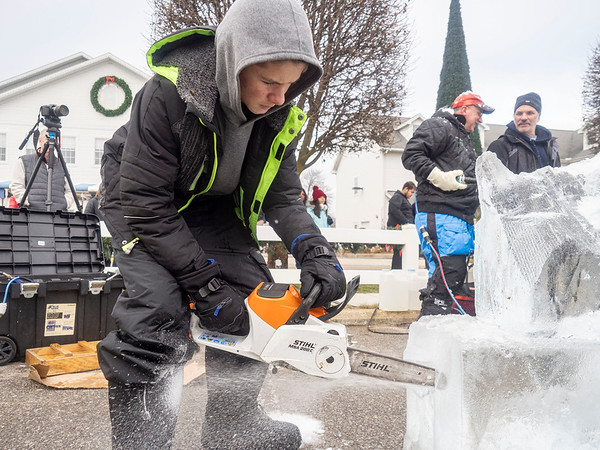 """Third generation ice sculpture Ethan Crumpacker, 13, of Avon, IN, carves out a portion of the """"Magical Reindeer, inspired by the spirit of the holidays"""" ice sculpture during the first day of the Shipshewana Ice Festival Friday. The """"Magical Reindeer"""" is the largest ice sculpture ever done in Shipshewana in front of the Blue Gate Restaurant located at 195 N. Van Buren St., in Shipshewana."""