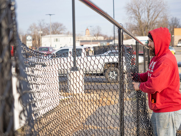 Joseph Weiser | The Goshen News<br /> Steven Mabie, of Elkhart, erects the new chainlink fence that at the Linway Plaza in Goshen Friday. The fence is being erected do to conflict between the Oasis and the owner of the Linway Plaza.