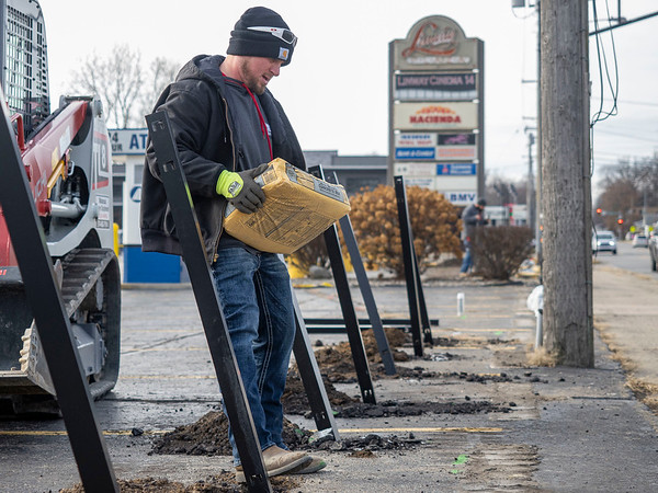 Joseph Weiser | The Goshen News<br /> Brandon Hall, of Elkhart, stages a bag of concrete for the new fence being at the Linway Plaza in Goshen Friday. The fence is being erected do to conflict between the Oasis and the owner of the Linway Plaza.