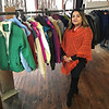 John Kline | The Goshen News<br /> Eliana Medrano, central registrar for Goshen Community Schools, poses in front of a display of winter coats recently donated as part of the school corporation's annual community winter clothing give-away program.
