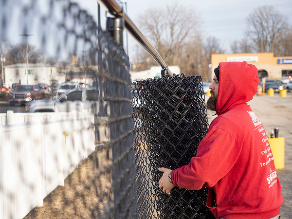 Joseph Weiser   The Goshen News<br /> Steven Mabie, of Elkhart, erects the new chainlink fence that at the Linway Plaza in Goshen Friday. The fence is being erected do to conflict between the Oasis and the owner of the Linway Plaza.