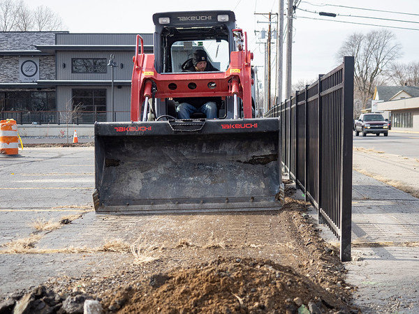 Joseph Weiser | The Goshen News<br /> Shawn West, of Elkhart, pushes dirt from the post holes for a new fence that was erected Thursday at Linway Plaza in Goshen Friday. The fence was the topic of a public hearing in October when the Indiana Department of Natural Resources was asked to review  if the 935 feet of fencing plaza owners Dave and Linda Wright are installing would be a problem in the Elkhart River's floodplain. The Wrights said they are installing the fence to delianate their property lines after the construction of The Oasis bar and restaurant in front of the plaza. The Oasis can be seen in the background.