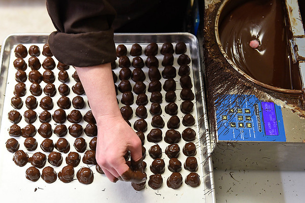 BEN MIKESELL | THE GOSHEN NEWS<br /> Nut Shoppe owner Danae Bell places cherry cordials on a tray after dipping them in chocolate Wednesday afternoon in her shop on Main Street in Goshen.