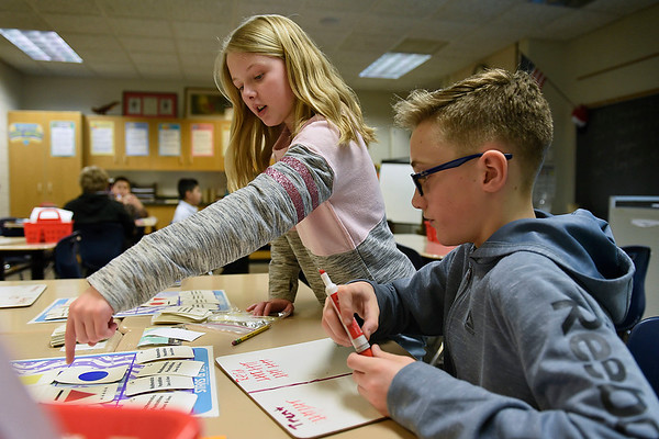 BEN MIKESELL | THE GOSHEN NEWS<br /> Sixth-grader Anna Stone helps classmate Reid Sollars tally up his score while playing a mathetmatics game, Stars and Bars, in Brayden Decker's class during Math Day Monday afternoon at Concord Intermediate School. The entire school participated in mathematics-themed activities, including the game in Decker's class, which focused on matching skills and patterns.