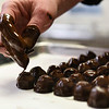 BEN MIKESELL | THE GOSHEN NEWS<br /> Nut Shoppe owner Danae Bell places cherry cordials on a tray after dipping them in chocolate Wednesday afternoon in their shop on Main Street in Goshen.