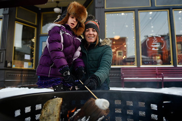 BEN MIKESELL | THE GOSHEN NEWS<br /> Amanda Sensenig, of Goshen, roasts marshmallows with her daughter Carly, 7, while enjoying First Friday's Hygge Fest outside the Electric Brew in Goshen. Electric Brew owners Myron and Dana Bontrager set up a fire pit and hot chocolate stand to warm up the crowds attending First Friday activities themed around coziness.
