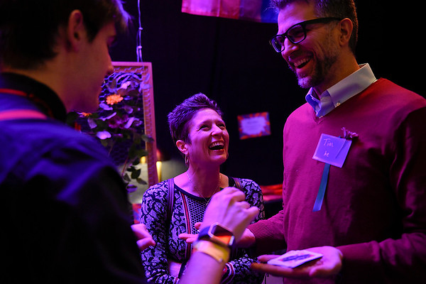 BEN MIKESELL | THE GOSHEN NEWS<br /> Jen Drescher, left, and her husband Tim, of Goshen, laugh as they watch a card trick from Goshen College sophomore Hugh Birky during the Masquerade Unmasked fundraiser for Mosaic Health & Healing Arts Saturday evening at Goshen Theater.