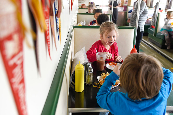 BEN MIKESELL | THE GOSHEN NEWS<br /> Parkside Elementary first-grader Poppy Habecker, center, sits with Zeke Shannon as they enjoy their curly fries and phosphate sodas they made on a field trip Thursday morning at the South Side Soda Shop.