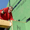 BEN MIKESELL | THE GOSHEN NEWS<br /> Merlin Swartzentruber, Goshen, with Hope Builders Group, Inc., works on a porch beam Tuesday afternoon at a house being constructed on River Race Drive in Goshen.