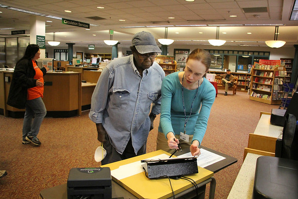SHEILA SELMAN | THE GOSHEN NEWS Voter outreach coordinator Kelsey McClure, right, explains the sign-in process for the new voting machines to Goshen resident Barnabas Muntu Thursday night at Goshen Public Library.