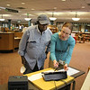 SHEILA SELMAN | THE GOSHEN NEWS<br /> Voter outreach coordinator Kelsey McClure, right, explains the sign-in process for the new voting machines to Goshen resident Barnabas Muntu Thursday night at Goshen Public Library.