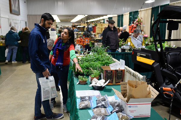 BEN MIKESELL | THE GOSHEN NEWS Poorna Bhagat, right, points out different plants for sale to Neel Bhagat, left, Saturday morning while walking through the Elkhart County Garden Expo at the Elkhart County 4-H Fairgrounds.